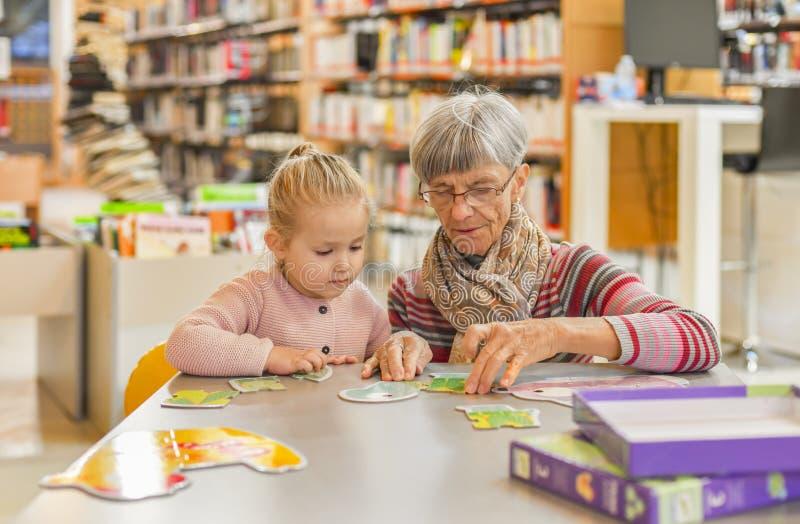 孙女和祖母在图书馆汇集难题 免版税库存图片