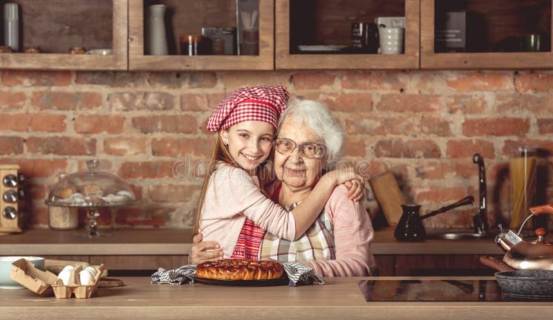 孙女拥抱她愉快的祖母 免版税库存照片