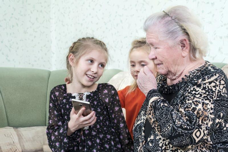 孙女教曾祖母使用电话 免版税图库摄影