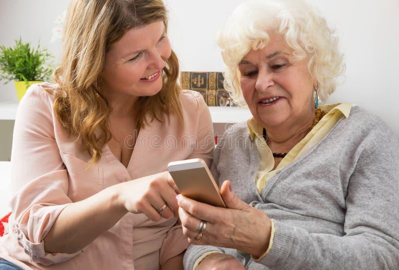 孙女教的祖母如何使用智能手机 免版税库存图片