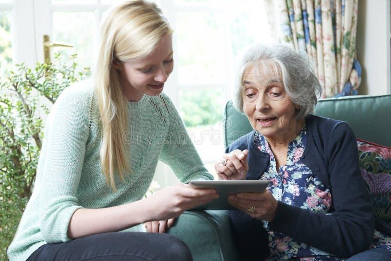 孙女显示祖母如何使用数字式片剂 库存图片
