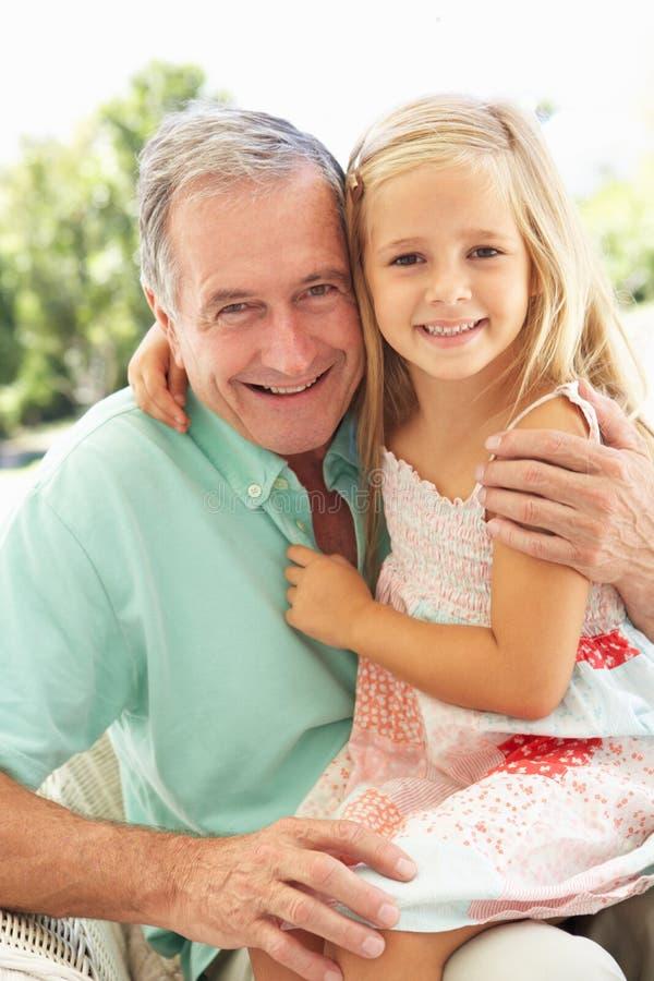 孙女祖父一起放松 免版税库存照片