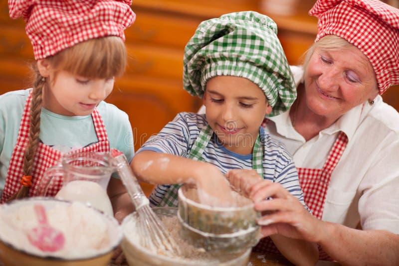 孙子和孙女在厨房里亲吻他们的祖母 免版税图库摄影