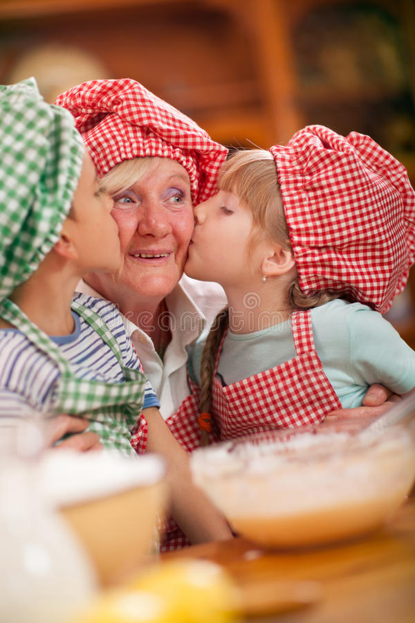 孙子和孙女在厨房里亲吻他们的祖母 免版税库存图片