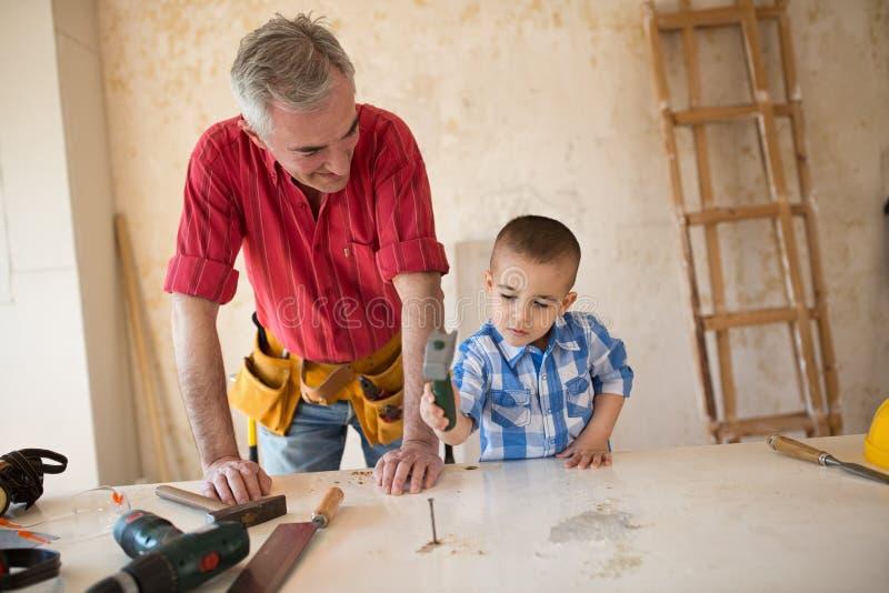 孙子在木匠` s车间帮助祖父 库存图片