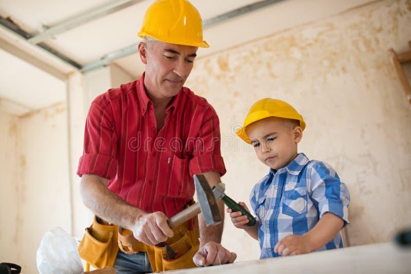 孙子在木匠` s车间帮助祖父 免版税图库摄影