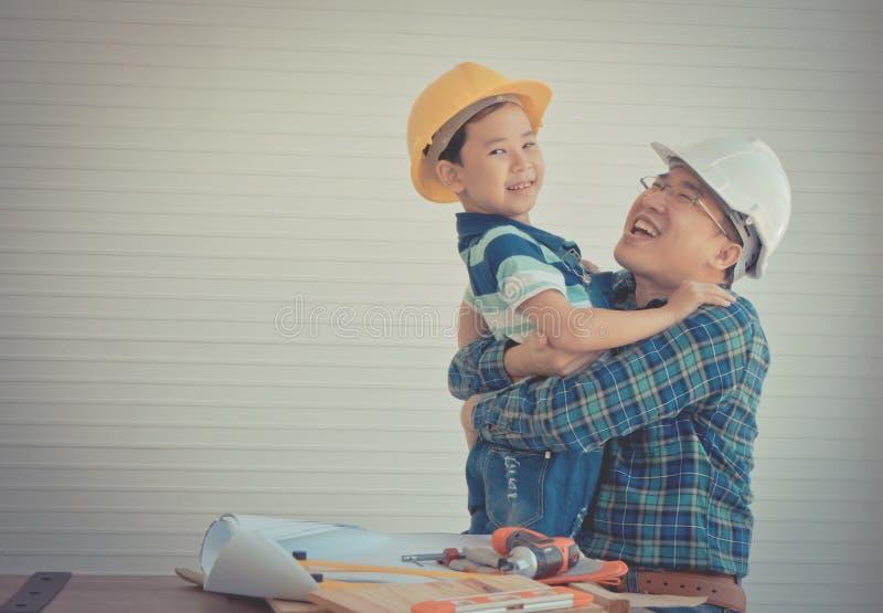 孙子抱父以复古语调对建筑行业概念的成功概念表示赞许。父子拥抱在建筑行业成功概念中的复古è 免版税库存照片
