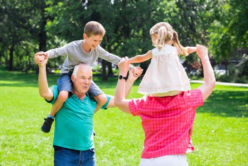 给孙的祖父母在公园扛在肩上乘驾 免版税库存图片