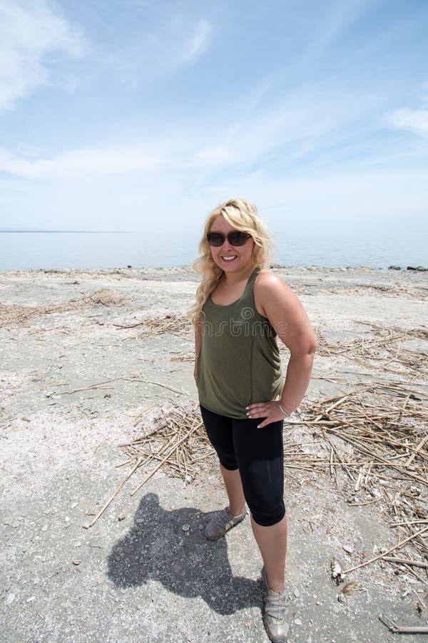 孟买海滩的白肤金发的女性,在索尔顿湖的一个杂乱海滩在加利福尼亚在一个热的夏日 库存图片
