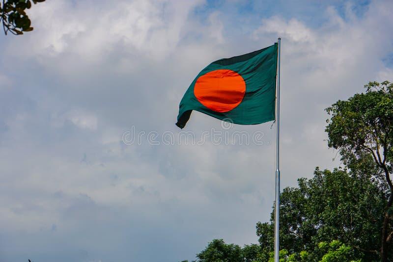 孟加拉国国旗。红绿旗在孟加拉蓝天飘扬。孟加拉国国旗。这面旗帜是绿色的背景,红色的圆圈象å 免版税库存图片