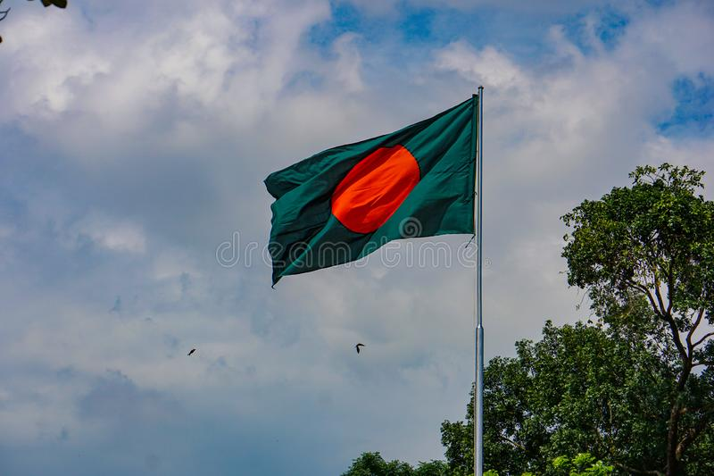 孟加拉国的国旗 红色绿色旗子是在孟加拉的天空蔚蓝的飞行 库存图片
