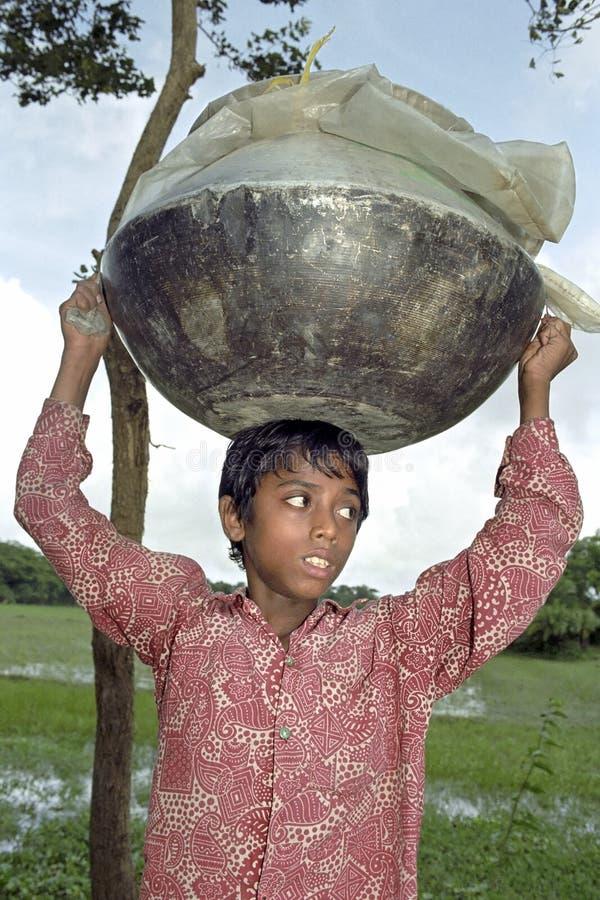 孟加拉国的男孩走动到把手与大平底锅 免版税库存照片