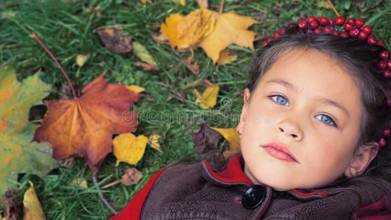 季节和人概念 说谎在地面上的一件红色外套的小女孩报道用黄色秋叶 免版税库存图片