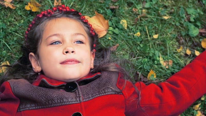 季节和人概念 说谎在地面上的一件红色外套的小女孩报道用黄色秋叶 图库摄影