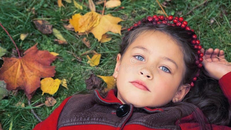 季节和人概念 说谎在地面上的一件红色外套的小女孩报道用黄色秋叶 库存图片