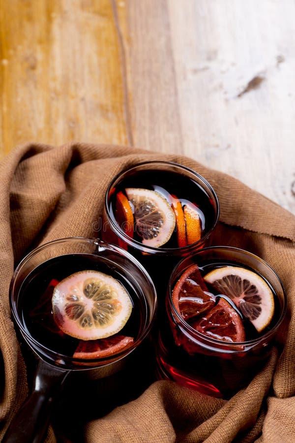 季节性和假日概念圣诞节与美好的橙色切片的加香料的热葡萄酒在玻璃里面,盖用温暖的白色围巾 免版税库存图片