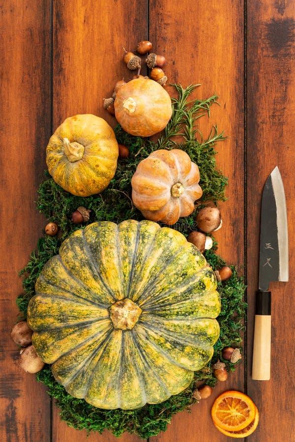 季节性成份顶视图南瓜、胡桃和准备好的蘑菇汤的雕刻与日本刀子 库存照片