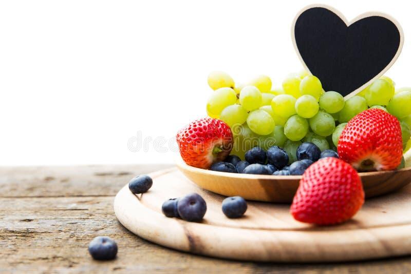 季节性果子的新混合在一个碗的在木桌,心脏si上 免版税库存照片