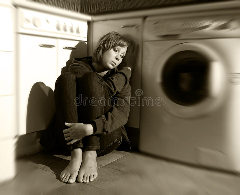 孤独和病的妇女坐在重音消沉和悲伤的厨房地板 免版税库存图片
