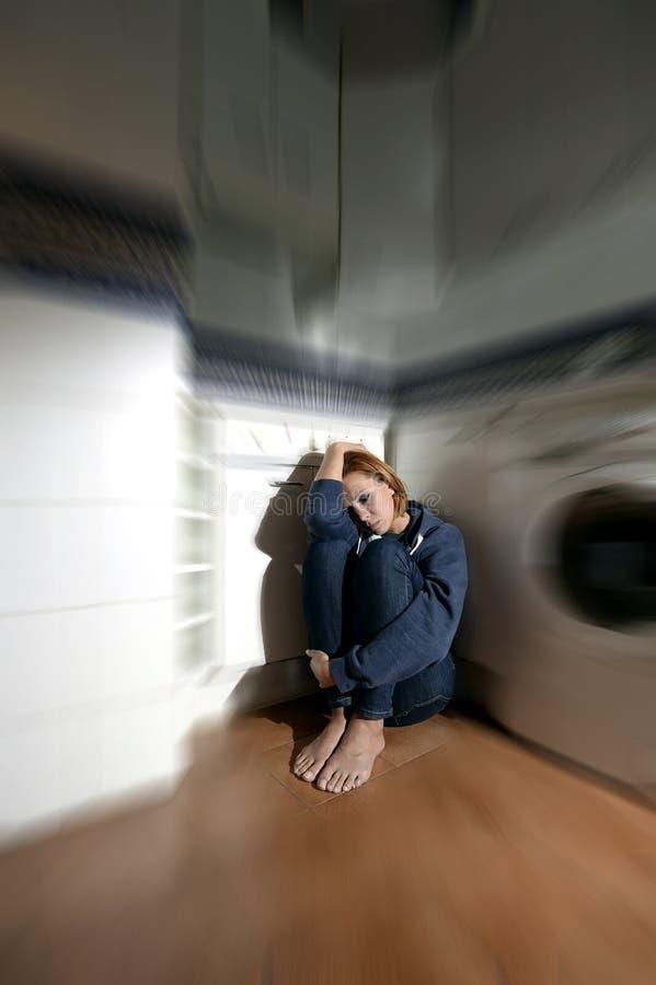 孤独和病的妇女坐在重音消沉和悲伤的厨房地板 库存照片