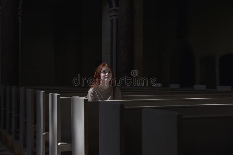 孤独年轻美丽的红发的女孩在祈祷的教会里坐 免版税库存图片