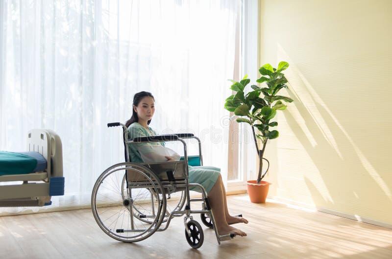 孤独的亚裔妇女患者断胳膊,当坐在轮椅在医院时 免版税图库摄影