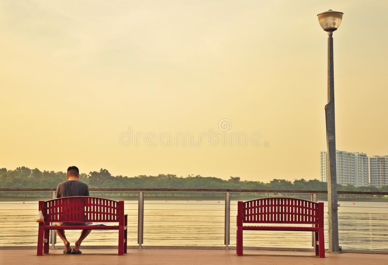 孤独的人坐有另一把空的椅子的一个甲板 免版税库存图片