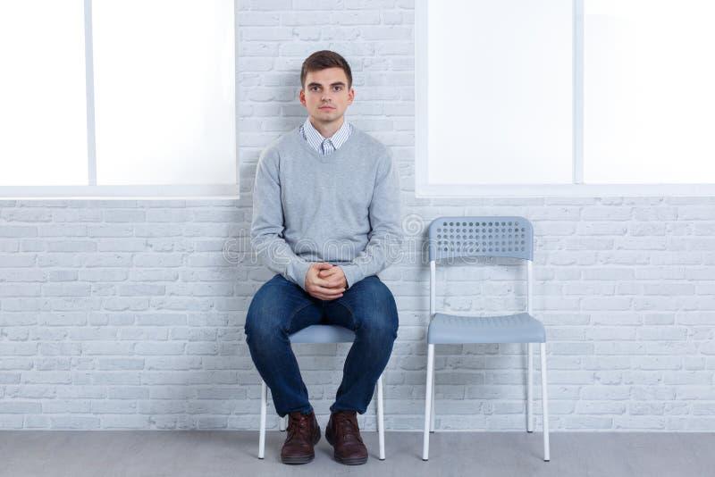 孤独的人坐椅子在一把空的椅子旁边 库存照片