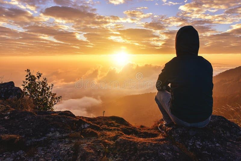 孤独的人坐观看的日出的一座山观看在温暖的单独,成功和和平概念 免版税图库摄影
