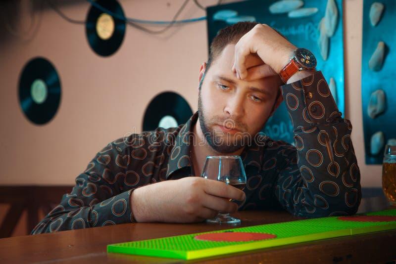孤独的人醉得在与杯的一个酒吧白兰地酒 库存照片