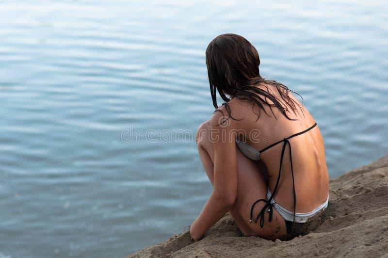 孤独的十几岁的女孩坐海滩 免版税库存照片