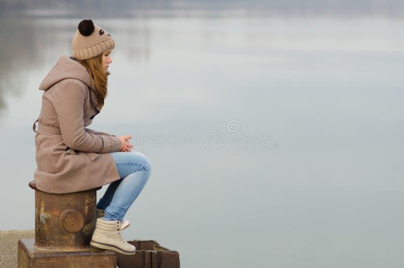 孤独的十几岁的女孩坐船坞 库存照片