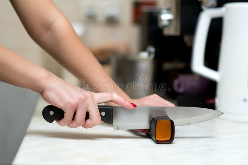 孤独的女人做男人的工作,磨刀 库存照片