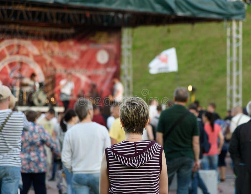 孤独的女孩回来与短发在街道摇滚乐音乐会 库存照片