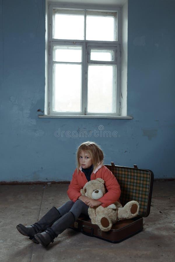 孤独的女孩坐手提箱 免版税库存图片
