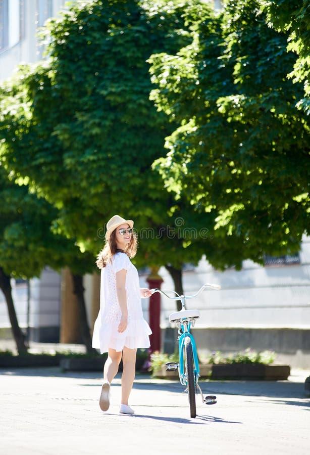 孤独的女孩来与在晴朗的城市街道上的减速火箭的自行车 图库摄影