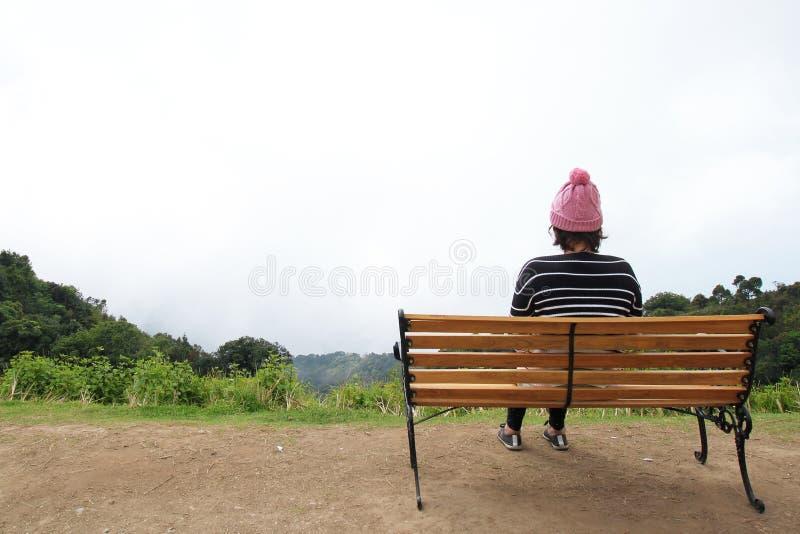 孤独的妇女单独坐山 免版税库存照片