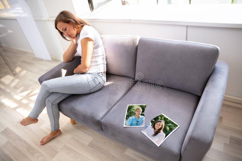 孤独的妇女坐沙发 免版税库存照片