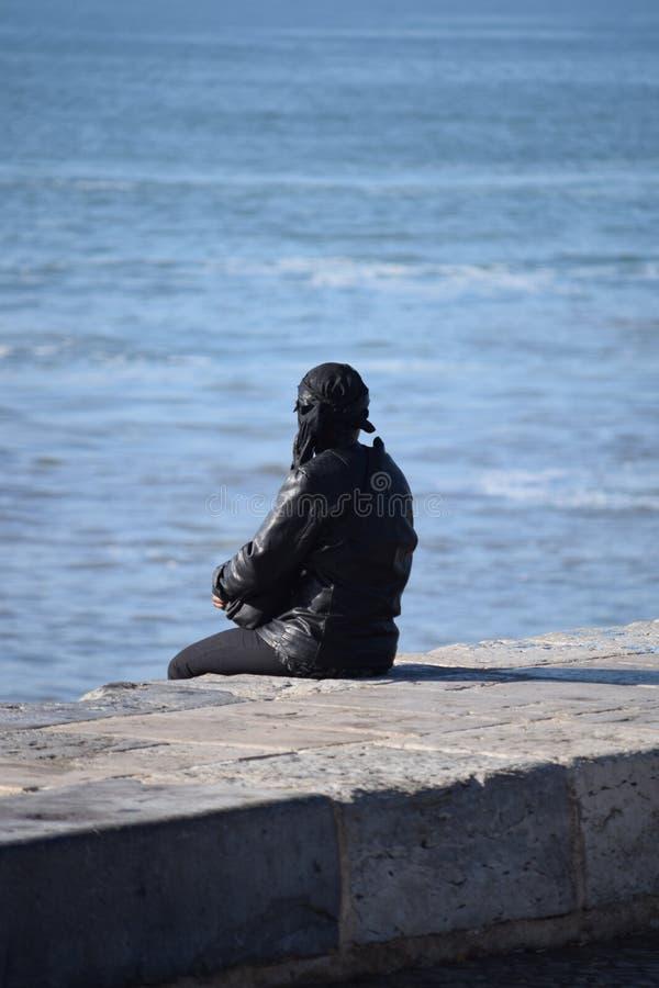 孤独的妇女坐防波堤 库存图片