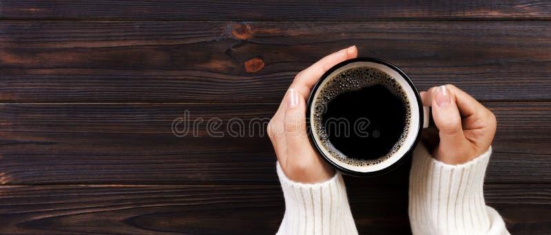 孤独的妇女饮用的咖啡早晨,拿着杯子在木书桌上的热的饮料的女性手顶视图  钞票 免版税库存图片
