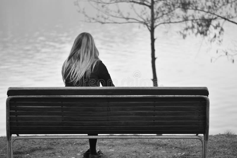 孤独的妇女,坐长凳,哀伤地看湖 库存图片
