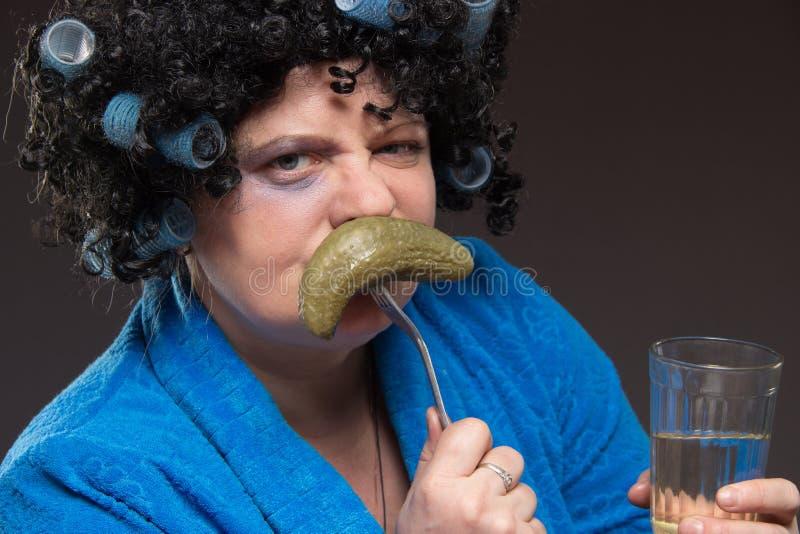 孤独的妇女从伏特加酒和eatin玻璃翻转者喝着 图库摄影