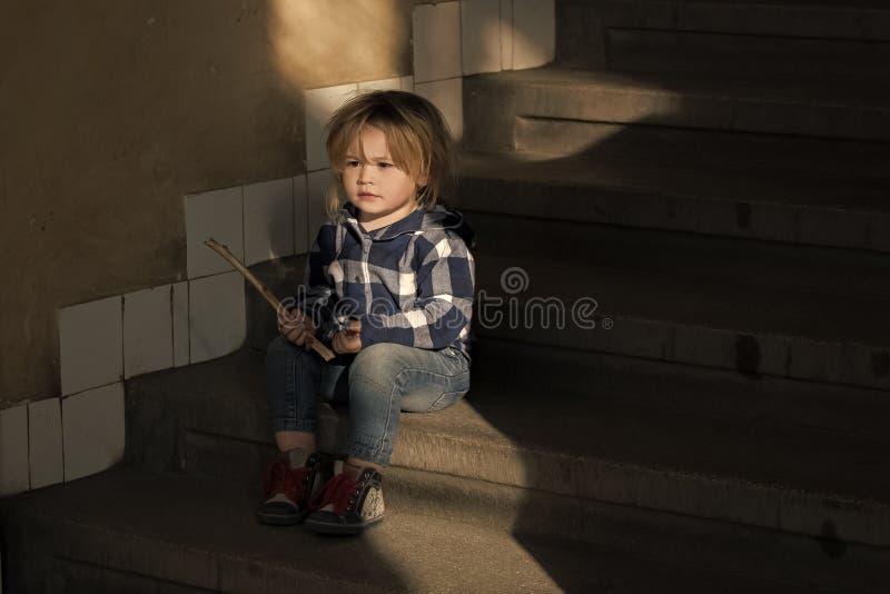孤独的子项 有金发的男孩坐房子台阶 免版税图库摄影