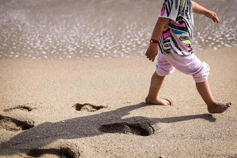 孤独的孩子在海滩走 库存照片