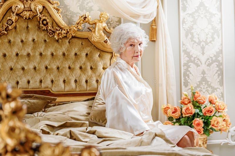 孤独的富有的资深夫人在卧室 库存图片