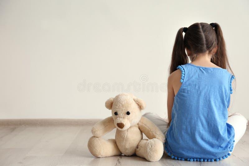孤独的小女孩坐地板在屋子里 免版税库存照片