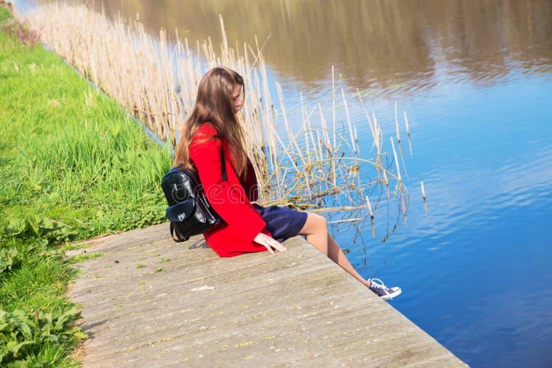 孤独的年轻十几岁的女孩坐河岸 免版税库存图片