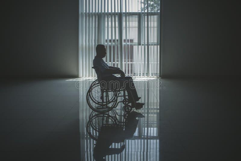 孤独的年长人看起来哀伤在轮椅 免版税库存照片