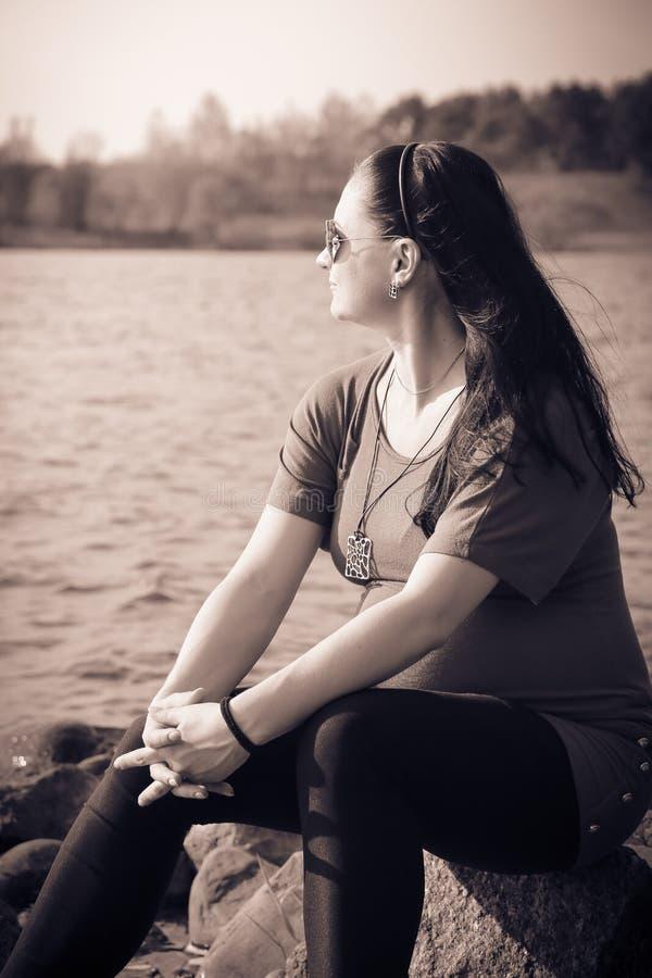 孤独的怀孕的女孩坐湖并且调查距离 库存图片