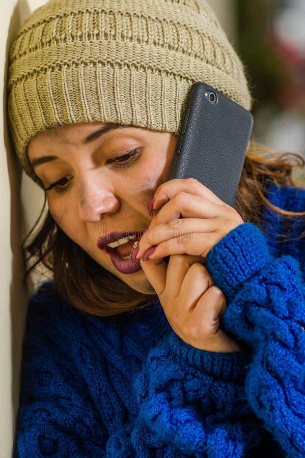 孤独的无家可归的妇女画象在街道上的在穿一蓝色有冠乌鸦和使用她的手机的冷的秋天天气在 库存图片